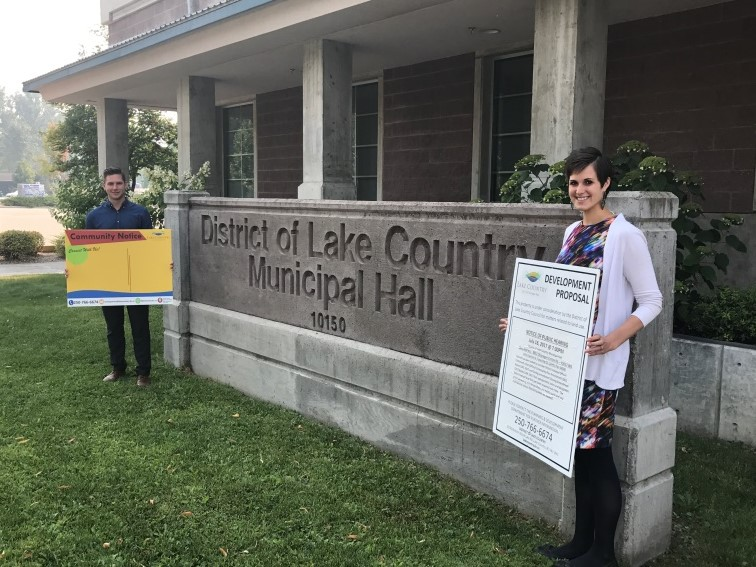 AJ Taylor and Jocelyn Ratzlaff display new and old development notification signs